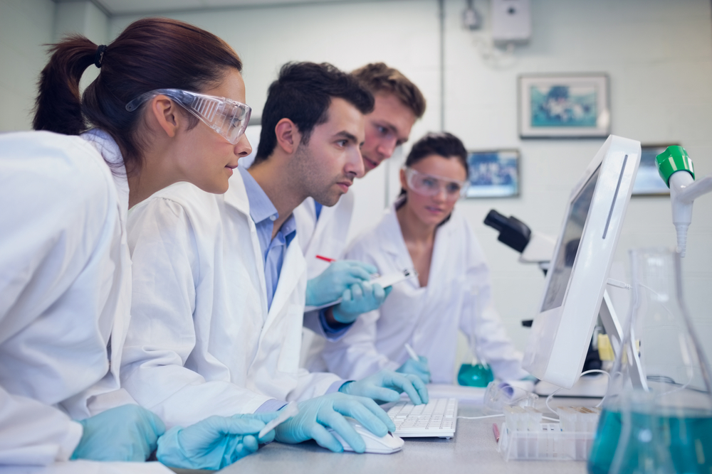 Side view of serious researchers looking at computer screen in the laboratory